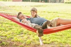 Vader en jonge zonen in hangmat stock fotografie