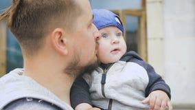 Vader en jonge zoon Een mens met een baard, die een baby in zijn wapens houden, stock video