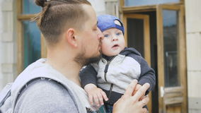 Vader en jonge zoon Een mens met een baard, die een baby in zijn wapens houden, stock videobeelden