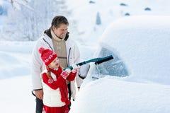 Vader en kind die van auto in de winter borstelen royalty-vrije stock fotografie