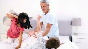 Vader en kinderen die een hoofdkussenstrijd in het bed hebben stock video