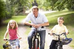 Vader en kinderen die fietsen in platteland berijden royalty-vrije stock foto's