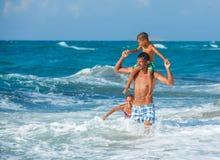 Vader en kinderen die in het overzees spelen royalty-vrije stock afbeelding
