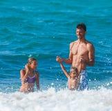Vader en kinderen die in het overzees spelen Royalty-vrije Stock Fotografie