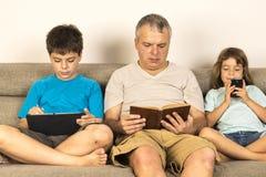 Vader en kinderen die op de bank zitten Royalty-vrije Stock Afbeeldingen