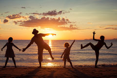 Vader en kinderen die op het strand in de zonsondergangtijd spelen Royalty-vrije Stock Foto's