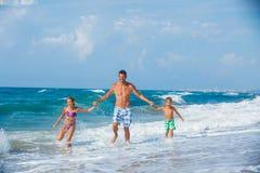 Vader en kinderen die op het strand spelen Stock Afbeelding