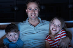 Vader en Kinderen die op Programma over TV Tog letten Stock Foto's