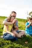 Vader en kinderen die proberen te fluiten Stock Afbeeldingen