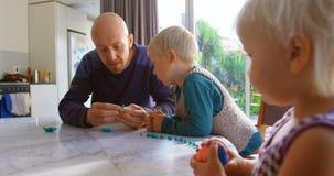 Vader en kinderen die samen met klei in een comfortabel huis 4k spelen stock video