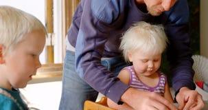 Vader en kinderen die samen met klei in een comfortabel huis 4k spelen stock videobeelden