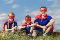 Vader en kinderen die superhero spelen in de dagtijd Stock Afbeelding