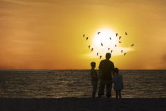 Vader en kinderen die van mooie zonsondergang genieten royalty-vrije stock fotografie