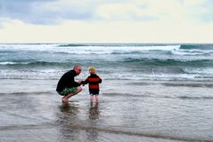Vader en Klein Kind bij Strand met Oceaanhorizon royalty-vrije stock afbeeldingen