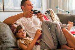 Vader en leuk weinig dochter die digitale apparaten thuis met behulp van royalty-vrije stock fotografie