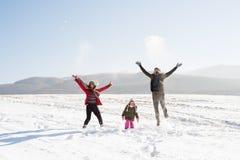 Vader en moeder met hun dochter, die in de sneeuw spelen stock afbeeldingen