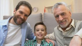 Vader en opa die jongen koesteren en camera, familietijd thuis onderzoeken stock footage
