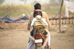 Vader en schoolmeisje berijdende motor in dorp royalty-vrije stock foto