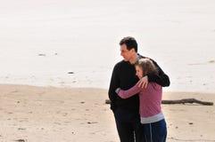 Vader en tienerdochter bij het strand royalty-vrije stock afbeelding