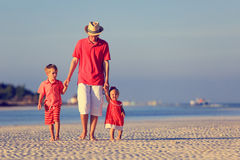 Vader en twee jonge geitjes die op de zomerstrand lopen Stock Foto