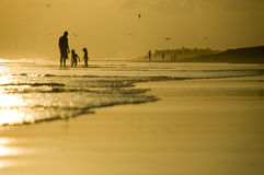 Vader en twee jonge geitjes die op het strand spelen Royalty-vrije Stock Afbeeldingen