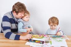 Vader en twee jongenssiblings die pret het schilderen hebben Royalty-vrije Stock Foto's