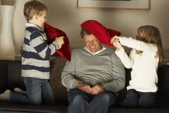 Vader en Twee Kinderen in de Strijd van het Hoofdkussen Stock Afbeelding