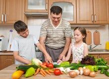 Vader en twee kinderen, meisje en jongen, die pret met vruchten en groenten in het binnenland van de huiskeuken hebben Gezond voe stock foto
