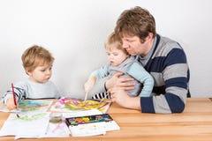 Vader en twee kleine jongenssiblings die pret het schilderen hebben Stock Afbeelding