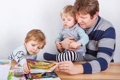 Vader en twee kleine jongenssiblings die pret het schilderen hebben Royalty-vrije Stock Afbeeldingen
