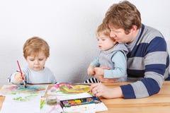 Vader en twee kleine jongenssiblings die pret het schilderen hebben Royalty-vrije Stock Afbeelding