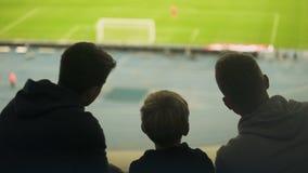 Vader en twee zonen die op voetbalwedstrijd letten samen, gelukkig weekend, vaderschap stock footage