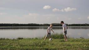 Vader en twee zoons speelvoetbal op het strand in de dagtijd Concept vriendschappelijke familie stock videobeelden