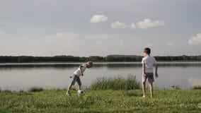 Vader en twee zoons speelvoetbal op het strand in de dagtijd Concept vriendschappelijke familie stock footage
