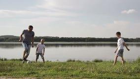Vader en twee zoons speelvoetbal op het strand in de dagtijd Concept vriendschappelijke familie stock video