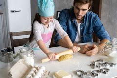 Vader en van weinig dochterbaksel gebakjes Pret in keuken hebben en familie die klaar voor een partij worden stock foto's