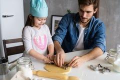 Vader en van weinig dochterbaksel gebakjes Pret in keuken hebben en familie die klaar voor een partij worden royalty-vrije stock foto's