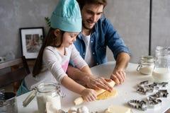 Vader en van weinig dochterbaksel gebakjes Pret in keuken hebben en familie die klaar voor een partij worden royalty-vrije stock afbeelding