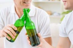 Vader en volwassen zoon het drinken bier stock foto's