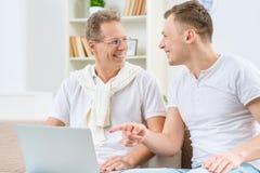 Vader en volwassen zoonszitting op de bank Royalty-vrije Stock Fotografie