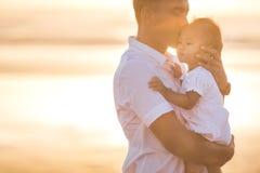 Vader en weinig babydochter op strand bij zonsondergang stock fotografie