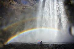 Vader en weinig dochter bij Skogafoss-waterval onder de regenboog, IJsland stock foto