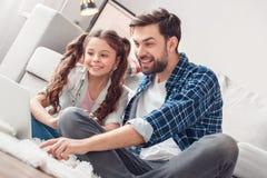 Vader en weinig dochter die thuis doorbladerend Internet op gelukkig laptop zitten stock afbeelding