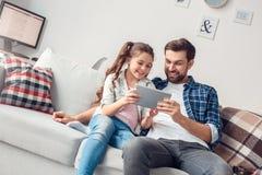 Vader en weinig dochter die thuis speelspel op digitale gelukkige tablet zitten stock foto