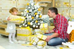 Vader en weinig dochter met dichtbij verfraaid van giftdozen Kerstboom thuis stock afbeelding