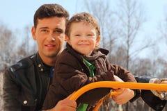 Vader en weinig zoon bij speelplaats Stock Foto