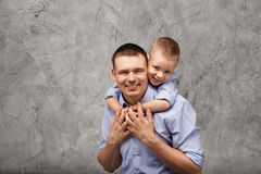 Vader en weinig zoon in blauwe overhemden voor grijze achtergrond Royalty-vrije Stock Fotografie