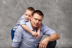 Vader en weinig zoon in blauwe overhemden voor grijze achtergrond Stock Afbeeldingen