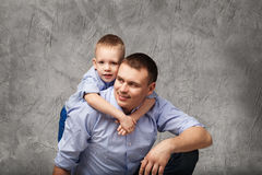 Vader en weinig zoon in blauwe overhemden voor grijze achtergrond Royalty-vrije Stock Foto