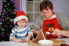 Vader en weinig zoon die een huis van het peperkoekkoekje voorbereiden Royalty-vrije Stock Afbeeldingen